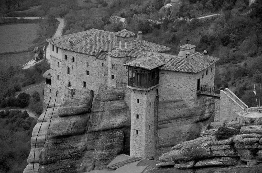 A black and white photo of a Monastery in Meteora built on the top of huge rock.