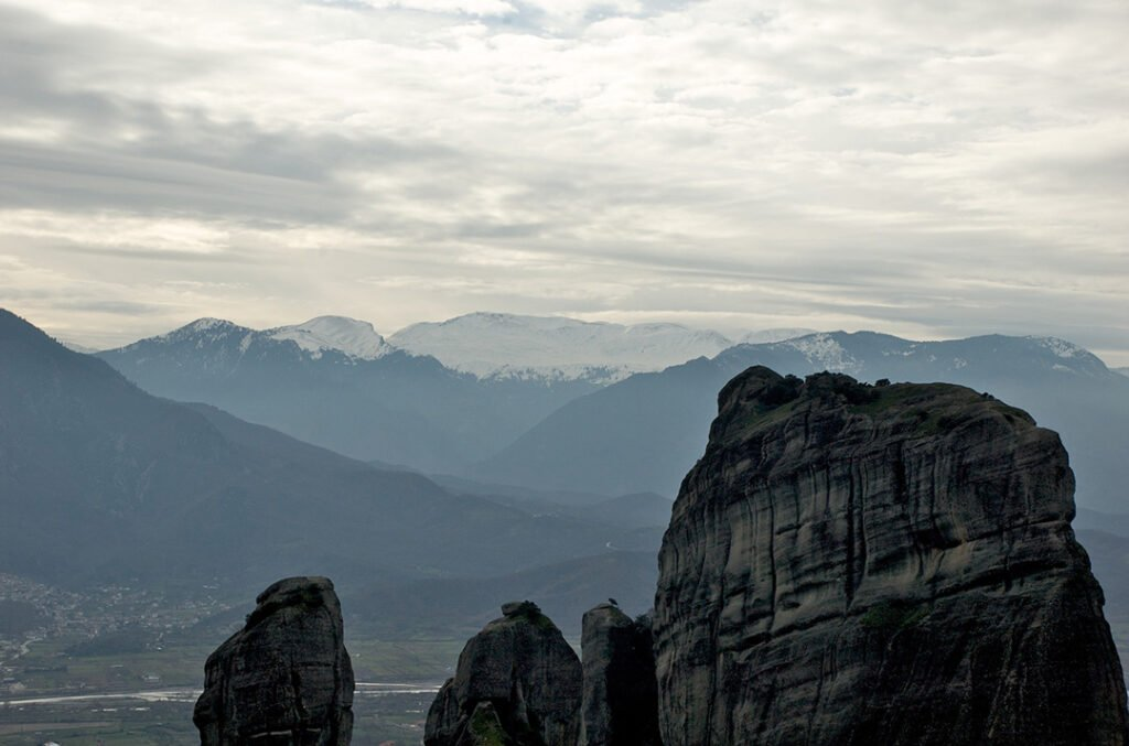 The huge rocks in Meteora, the mountains of the region and a cloudy sky.